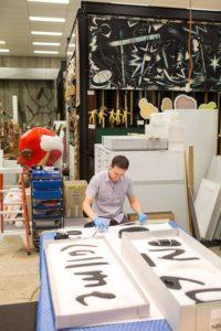 Artbank registrar packs a work by Shaun O'Connor for transport
